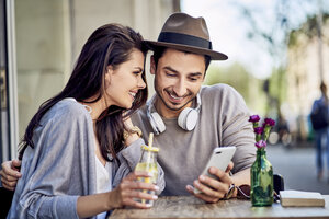 Happy young couple looking at cell phone at outdoors cafe - BSZF00787