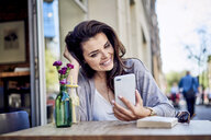 Happy woman looking at cell phone at outdoors cafe - BSZF00796