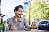Happy young man using cell phone at outdoors cafe - BSZF00799
