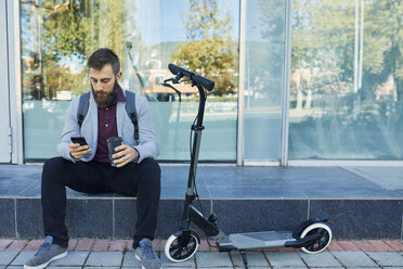 Businessman sitting outdoors using cell phone next to scooter - ZEDF01702
