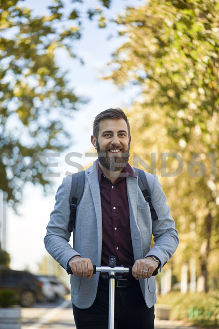 Portrait of smiling businessman with scooter - ZEDF01714