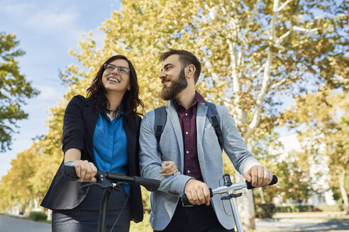 Happy businessman and businesswoman with scooters - ZEDF01717