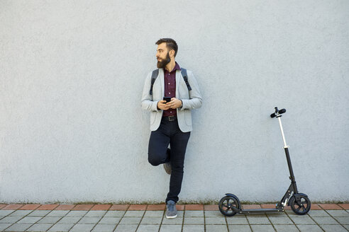 Businessman with scooter and cell phone leaning against a wall - ZEDF01720