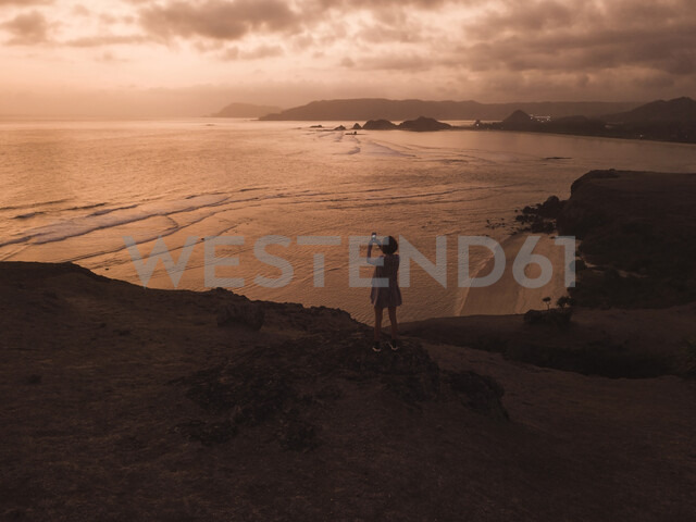 Indonesia, Lombok, young woman at coast at sunset - KNTF02280