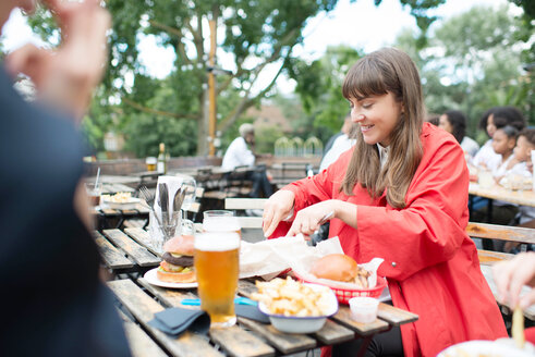 Young woman eating at outdoor restaurant - LUXF01727