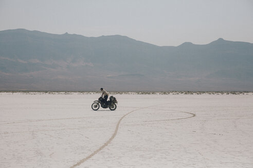 Side view of biker riding motorcycle on road against clear sky - CAVF51498
