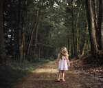 Girl standing on dirt road amidst forest - CAVF51504