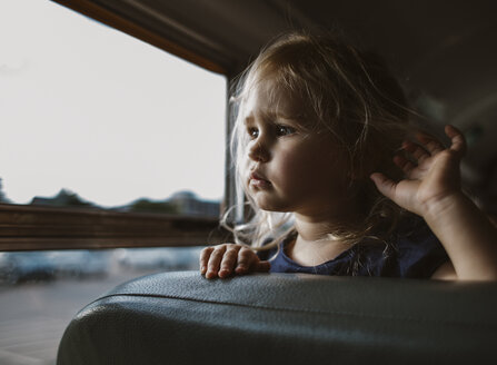 Close-up of girl looking through window while standing in bus - CAVF51510
