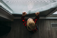 High angle view of boy looking through window while standing at home during winter - CAVF51540