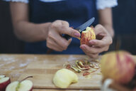 Close-up of woman's hands cutting apple for preparing cinnamon bun at home - CAVF51546