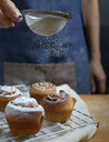Close-up of hand sieving icing sugar on cinnamon buns - CAVF51549