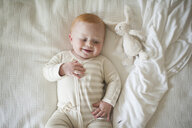 Overhead view of cute baby boy lying on bed - CAVF51555