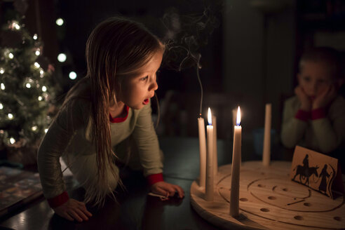 Sister blowing candles on table during Christmas with brother in background - CAVF51576