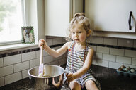 Portrait of cute girl preparing food in container while sitting on kitchen counter at home - CAVF51591