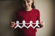 Girl holding paper chain while standing against wall at home - CAVF51684