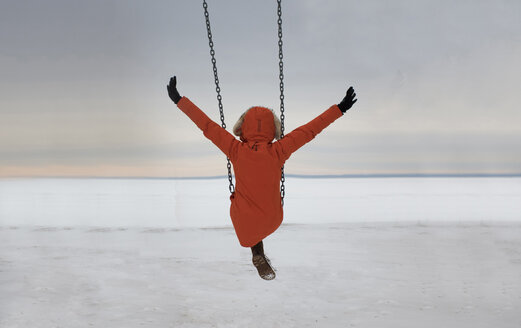 Rear view of woman with arms outstretched swinging over snow covered landscape against cloudy sky - CAVF51723