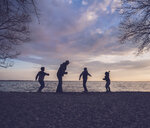 Father and son playing at lakeshore against cloudy sky - CAVF51780