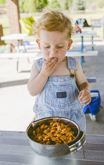 Cute boy wearing bib overalls while eating crackers from bowl - CAVF51789