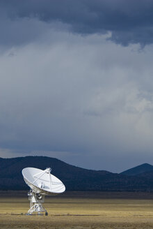 Satellite dish on field against cloudy sky at dusk - CAVF51792