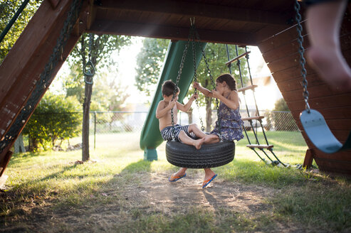 Playful siblings swinging on tire swing at playground - CAVF51837