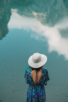High angle view of young woman wearing hat while standing against lake - CAVF51849