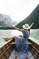 Happy woman enjoying rowboat riding over lake against mountains - CAVF51852