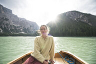 Woman sitting in boat on river amidst mountain against sky - CAVF51855