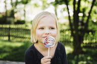 Close-up of girl looking away while eating lollipop - CAVF51858