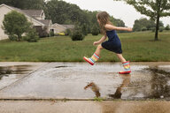 Side view of girl jumping in puddle at footpath - CAVF51870
