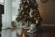 Girl playing with toys against Christmas tree at home - CAVF51966