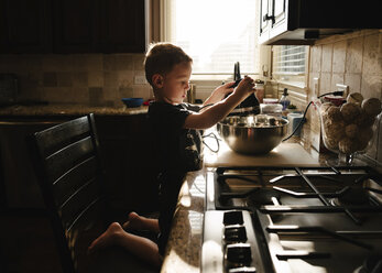 Side view of boy preparing food in kitchen at home - CAVF52026