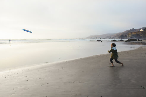 Boy throwing Frisbee while standing on shore at beach against sky - CAVF52035