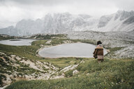 Rear view of woman with blanket standing on grassy field by lake against cloudy sky - CAVF52044