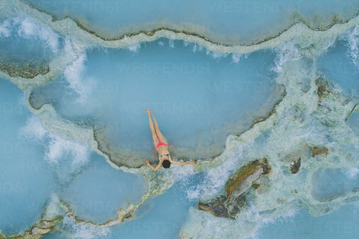 High angle view of teenage girl wearing bikini while relaxing in hot spring - CAVF52053 - Cavan Images/Westend61