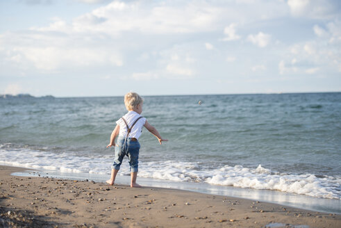 Rear view of baby boy throwing stone in sea while standing at beach against cloudy sky - CAVF52098