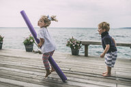 Siblings playing on wooden pier by sea - CAVF52143