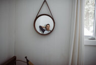 Thoughtful man reflecting on mirror at home - CAVF52149