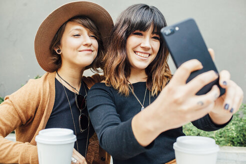 Smiling female friends taking selfie while sitting at table - CAVF52218