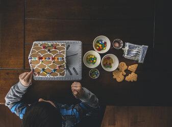Overhead view of boy making gingerbread house on wooden table during Christmas at home - CAVF52230