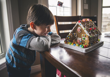 Happy boy looking at gingerbread house on wooden table during Christmas - CAVF52233