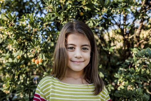 Portrait of girl standing against trees at park - CAVF52236