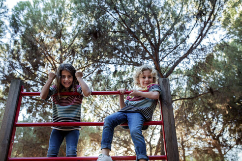 Low angle portrait of sisters balance on outdoor play equipment against trees at park - CAVF52239