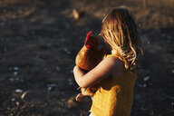 Side view of girl carrying hen while standing on field - CAVF52305