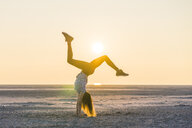 Side view of woman doing handstand at beach against clear sky during sunset - CAVF52314