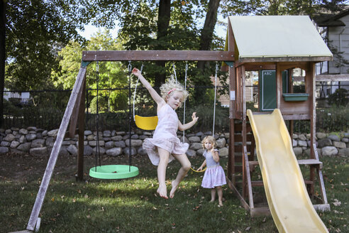 Sisters playing on swings at playground - CAVF52335