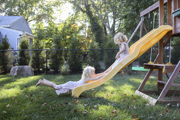 Sisters playing on slide at playground - CAVF52338