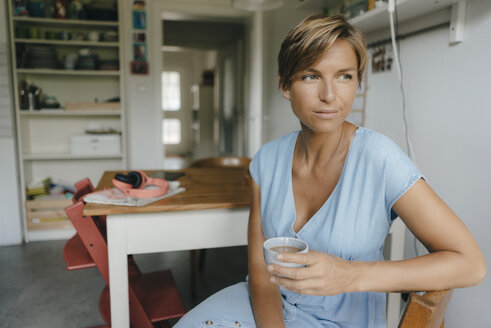 Woman sitting at table at home with cup of coffee - KNSF05040