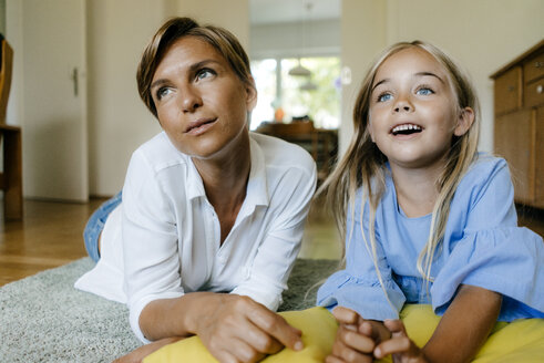 Mother and daughter lying on the floor at home watching something - KNSF05049