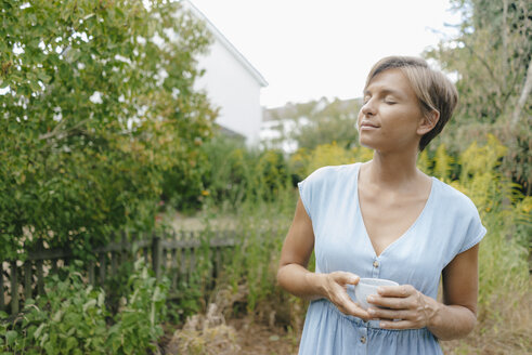 Woman with closed eyes standing in garden holding cup of coffee - KNSF05055