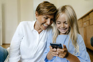 Laughing mother and daughter looking at smartphone together - KNSF05058